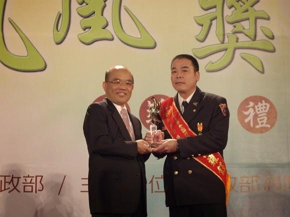 江耀鈺(右)於民國九十五年當選全國消防楷模,由時任台北縣長蘇貞昌(左)授獎。(江耀鈺提供)