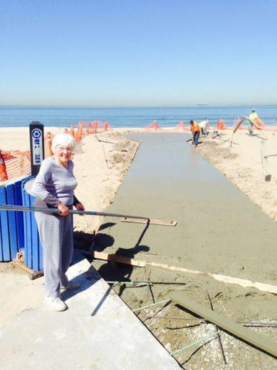 這張拍攝於海灘的照片中,一位白人老太太笑咪咪地拿著金屬管站在正在建造的無障礙步道旁,可見遠方正在施工的工作人員,以及背景一望無際的海與天。照片來源 Manhattan Beach Timeline 臉書粉絲頁。