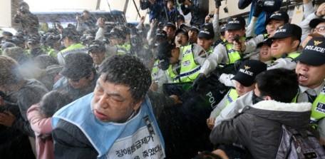 照片中捕捉了警察噴灑催淚瓦斯,試圖驅走抗議民眾。照片中抗議民眾與警察發生拉扯,周圍可見記者拿著相機拍攝 攝影: Kang Jae-hoon