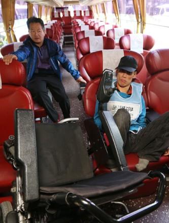 一名身障者坐在巴士內的椅子上,他的前方走道擺放著是傾斜的輪椅,可見走道與座位的狹小,無法讓他順利使用輪椅上車。斜後方做了另一位男士。身障者要上公車,需要司機協助。攝影 Yonhap