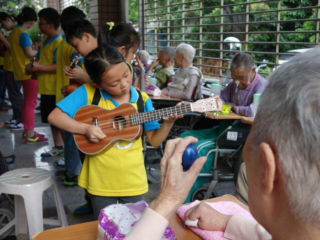 原來是孩子們到養護中心,除了幫銀髮的長者按摩外,也現場彈奏烏克麗麗。