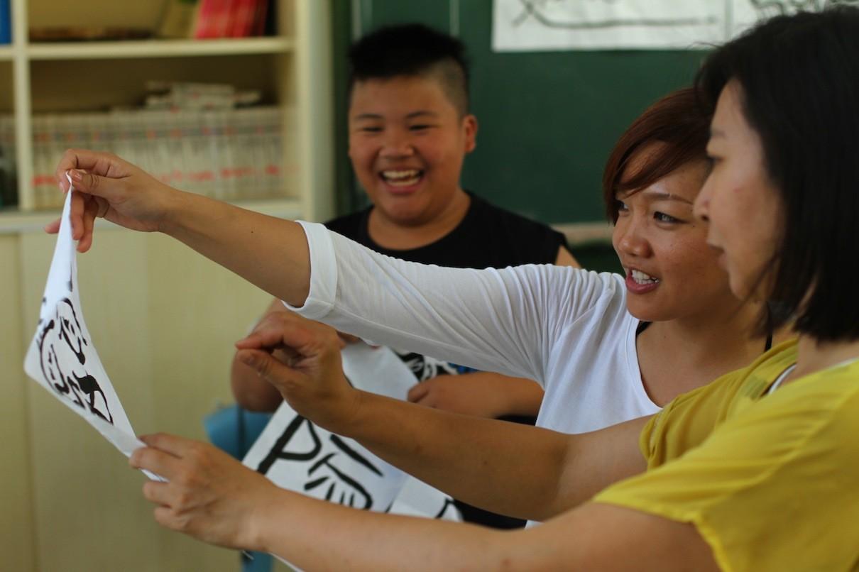 積極參與北濱校園活的歐媽〈中〉與佳玲老師〈右〉一起欣賞孩子寫的意象書法。