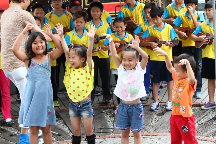 三年級以上的哥哥姐姐,正在作表演前的彩排,年幼的弟妹,聽著樂音,樂得手足舞蹈。