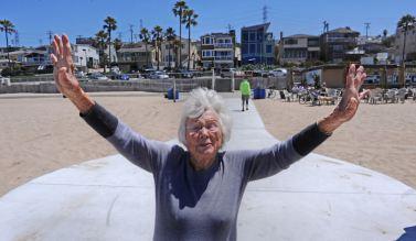 這張照片中有一位白髮的老太太張開雙臂站在海灘的無障礙步道上,背景可見沙灘、人群、房屋、藍天。攝影: Brad Graverson。