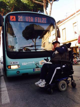 照片中一位男性電動輪椅使用者擋在一部巴士前,手拿著電話通話中。巴士有輪椅席位以及車路線號碼的標示。