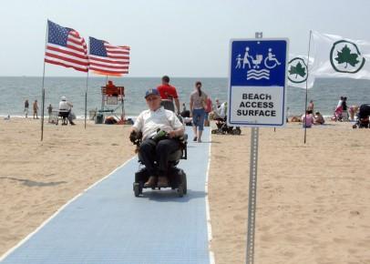 這張拍攝於沙灘上的照片,有一位電動輪椅使用者正在淡藍色的沙灘墊上步行,一旁可見美國國旗,令一旁是紐約市公園管理處的楓葉旗幟的標誌,背景可見海灘人潮與海。照片前景有一個樹立的標示,圖繪有海灘墊、輪椅使用者、家長與手推的娃娃車與小孩,標示文字是Beach Access Surface 可及海灘的鋪面步道。