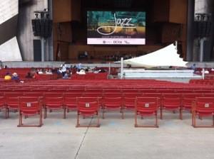 圖片敘述:從後排無障礙席位往舞臺正面照過去,中間有白色的舞台小搭棚,最後一排障礙者席位的固定座位旁有空格。舞台螢幕上打的是當日音樂會Jazz爵士樂大字的主題。