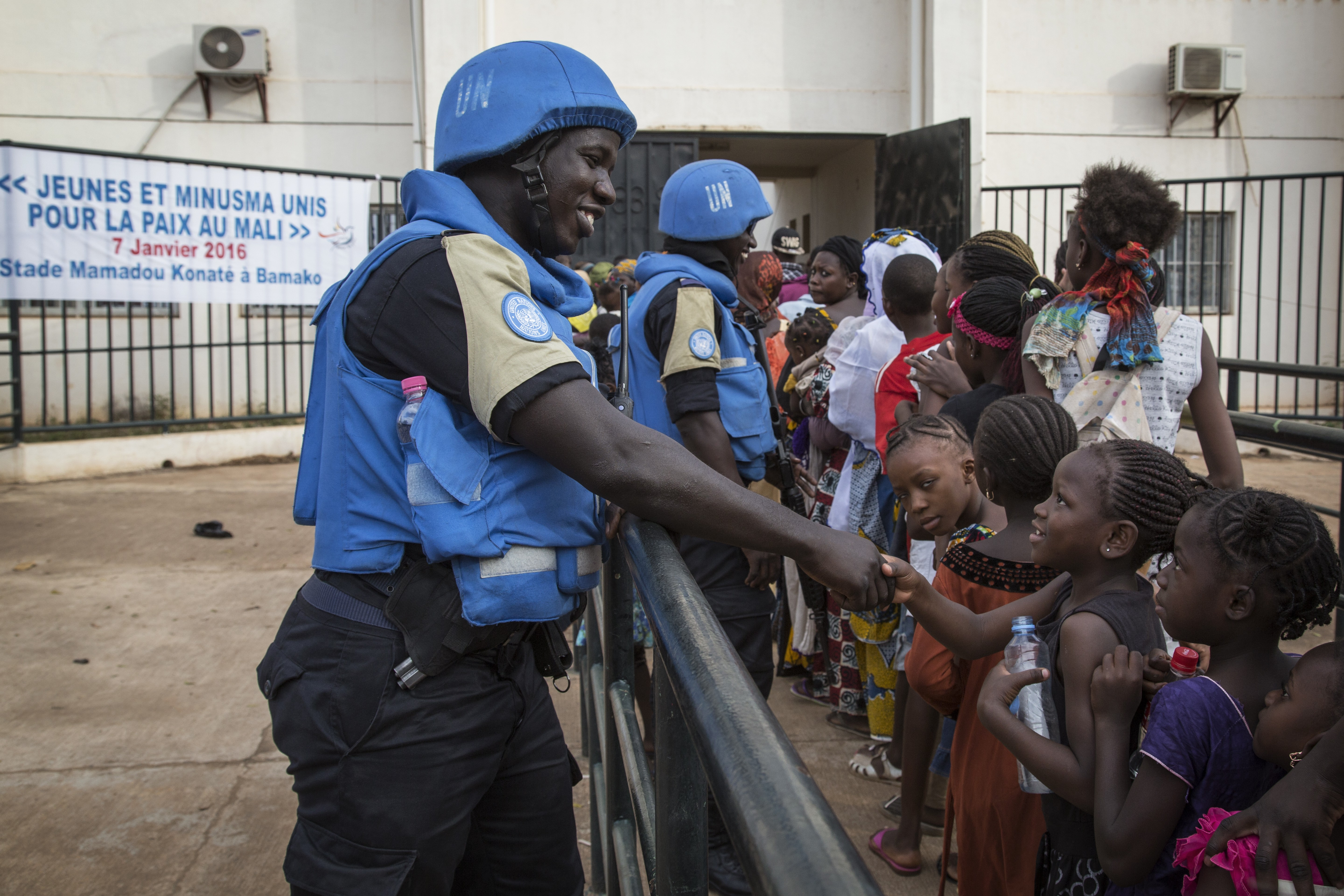 Senegalese peacekeepers from the UN Multidimensional Integrated Stabilization Mission in Mali (MINUSMA) Formed Police Unit (FPU) speak with Malians while they patrol outside Mamadou Konate Stadium during a sport event organized by the Outreach Unit to promote peace among the youth.